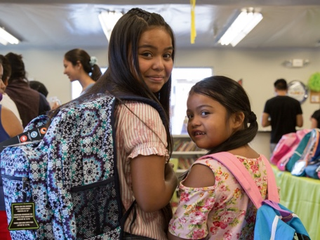 Photo of two girls wearing backpacks